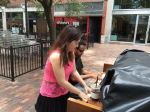 People playing outside pianos.